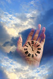 Hand of Time in the Clouds. Hand in the clouds with a roman numeral clock on the palm of the hand Royalty Free Stock Photos