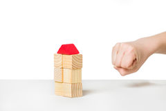 Hand about to destroy house made of wooden blocks. Human hand about to destroy house made of wooden blocks royalty free stock images