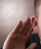 Hand to Ear Listening Stock Image