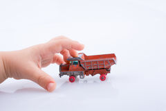 Hand is about to grab a red  toy truck. Baby hand is about to grab a red  toy truck on white background Stock Images