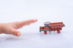 Hand is about to grab a red  toy truck. Baby hand is about to grab a red  toy truck on white background Royalty Free Stock Photos