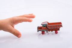 Hand is about to grab a red  toy truck. Baby hand is about to grab a red  toy truck on white background Stock Photos