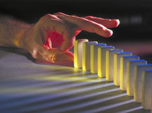 Hand about to knock down dominoes Stock Photo