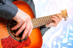 Hand to pluck the strings of a guitar. Male hand plucking guitar strings with fingers Stock Photos