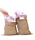 Hand to sacks with euro bills. Royalty Free Stock Image