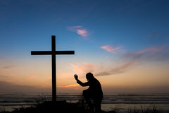 Hand to Salvation. Man praying with his hand up by a black cross on a beach with a dusk sky sunset behind it Stock Photography
