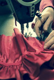 Hand About to Trim Excess Thread from a Sewn Cloth Royalty Free Stock Images