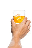 Hand toasting a glass of whiskey on the rocks Royalty Free Stock Photo