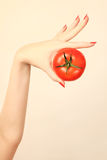 Hand tomato with red nails manicure stock photos