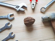 Hand, tool and big walnut on wooden background. The concept of complex problems, the challenge can be solved. Hand, tool and big walnut on wooden background Royalty Free Stock Photo