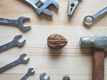 Hand, tool and big walnut on wooden background. The concept of complex problems, the challenge can be solved. Hand, tool and big walnut on wooden background stock photos