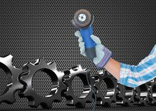 Hand with tool with metal and cogs background Stock Photos