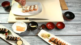 Hand with tool prepares sushi. stock footage