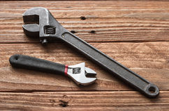 The hand tools. The steely adjustable wrenches on the wooden table Royalty Free Stock Photo