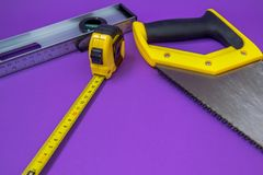 Hand tools yellow wood saw, stapler, tape measure royalty free stock photography