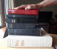 Swear on a stack of bibles. A hand on top of a stack of bibles is ready to swear the truth royalty free stock photos