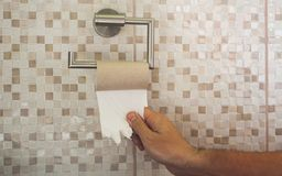 Hand with torn toilet paper royalty free stock photo
