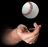 Hand Tossing Baseball. A male hand tossing a baseball up in the air on an isolated dark background - 3D render Royalty Free Stock Photos