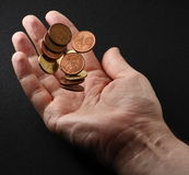 Hand tossing coins. Hand tossing Euro coins in the air against a black background Royalty Free Stock Photo