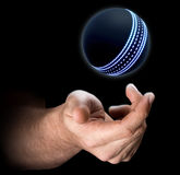 Hand Tossing Cricket Ball. A male hand tossing a futuristic cricket ball up in the air on an isolated dark background - 3D render Royalty Free Stock Images
