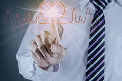 Hand touch the heart pulse. Businessman hand touch the heart pulse on futuristtic interface Stock Photography