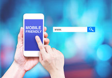 Hand touch mobile phone with mobile friendly word with search b. Ox at blurred blue background, Digital marketing business concept stock photos