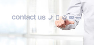 Hand touch screen display with contact us concept text Stock Photo