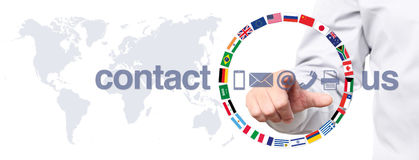 Hand touch screen display with global contact us concept text, f Stock Photos