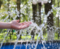 Hand touches clean and fresh water. Hand touches clean and fresh water from the fountain Stock Image
