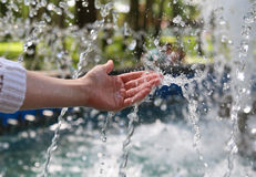 Hand touches clean and fresh water. Hand touches clean and fresh water from the fountain Royalty Free Stock Photography