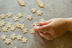 Hand touches flower from dough. Royalty Free Stock Image