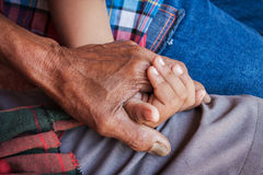 Hand touches and holds an old man wrinkled. Asian kids little boy hand touches and holds an old man wrinkled hand stock image