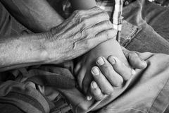 Hand touches and holds an old man wrinkled. Asian kids little boy hand touches and holds an old man wrinkled hands,black and white tone royalty free stock image