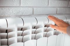 Hand touches the radiator. Female hand touches the radiator royalty free stock image