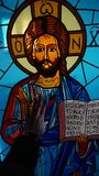 Hand touches the stained glass window with the image of a Saint in a Church in Cyprus royalty free stock image
