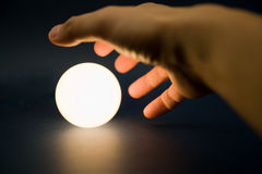 Hand touching a bright ball Stock Images