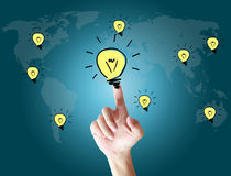 Hand touching bulb on the screen world Stock Photography