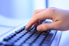 Hand touching computer keys. Close-up of hand touching computer keys Stock Images
