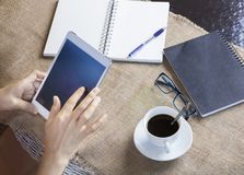 Hand touching on computer tablet screen with black coffee and pa Royalty Free Stock Images