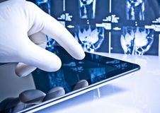 Hand touching digital tablet on x-ray images Stock Photo