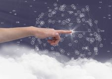 Hand touching digitally generated icon against sky background Stock Image