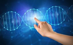 Hand touching DNA molecule. Female hand touching DNA molecule with blue background stock photography