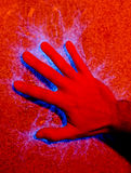 Hand touching electrically powered panel. Hand on electricity charged surface creating blue sparks Royalty Free Stock Image