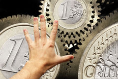 Hand touching euro coin gears Royalty Free Stock Images