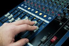 Hand touching faders in an audio mixing console Royalty Free Stock Image