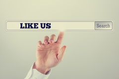 Hand touching with the finger the search bar with Like us text Stock Photos