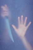 Hand touching frosted glass and holding knife. In the shadow Stock Photography