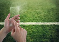 Hand touching glass screen on sports pitch. Digital composite of Hand touching glass screen on sports pitch Stock Images