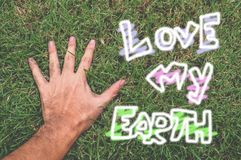Hand touching green grass field Royalty Free Stock Image
