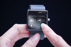 Hand touching home control application on smartwatch. Home automation is the use and control of home appliances remotely or automatically Royalty Free Stock Image